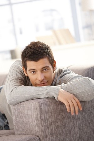 Portrait of handsome young man smiling on couch, looking at camera. Stock Photo - 8398192