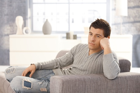Portrait of handsome young man sitting daydreaming on sofa in living room. Stock Photo - 8398171