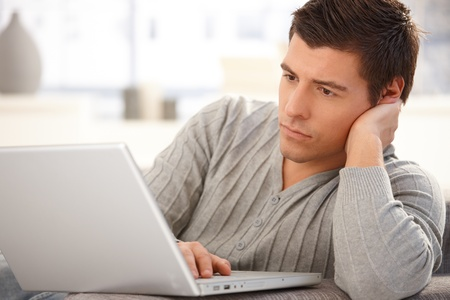 focusing: Portrait of goodlooking man focusing on laptop computer screen, typing on keyboard, looking serious.