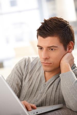 Goodlooking guy using laptop computer, looking at screen, thinking. Stock Photo - 8398144