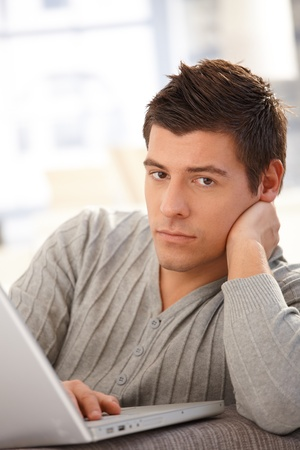 Portrait of handsome young man with laptop computer, looking at camera. Stock Photo - 8398153