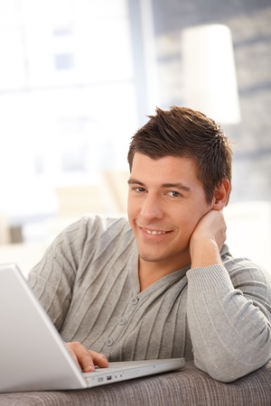1 man only: Portrait of young man using laptop computer at home, smiling at camera. Stock Photo