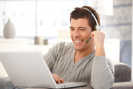 headset: Portrait of handsome young man using laptop computer with headset, laughing. Stock Photo