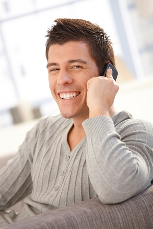 Portrait of laughing guy speaking on cellphone at home, looking at camera happily. photo