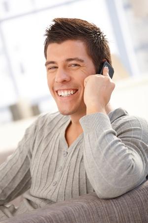hombre sentado: Retrato de hombre riendo hablando sobre el m�vil en casa, mirando la c�mara felizmente.