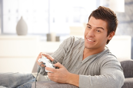 enjoy space: Young guy enjoying computer game, playing with joystick, smiling happily. Stock Photo