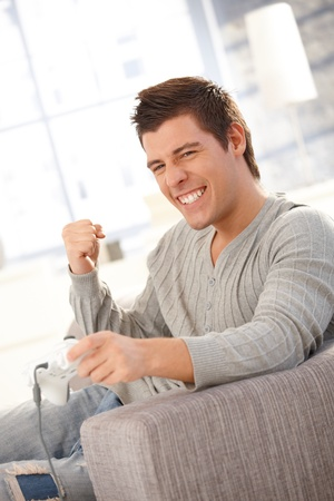 only young adults: Young man happy about winning in computer game at home, raising fist in triumph.