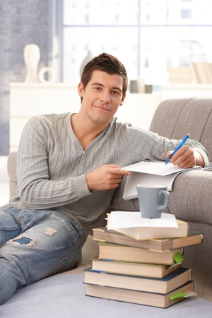 Portrait of smiling college student learning at home with pile of books, sitting on floor, taking notes, looking at camera. Stock Photo - 8398188