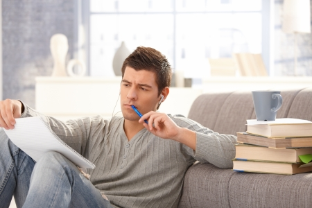 one adult: University student learning at home, holding notes and pen, listening to music. Stock Photo