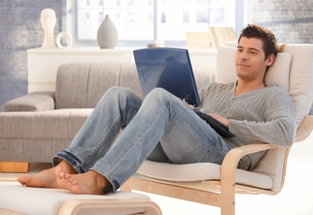 hombre sentado: Goodlooking joven relajante en casa en el sill�n, sentado en la sala de estar con el equipo port�til, sonriendo. Foto de archivo