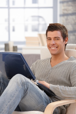 Portrait of happy guy sitting at home using laptop computer, smiling at camera. Stock Photo - 8398175