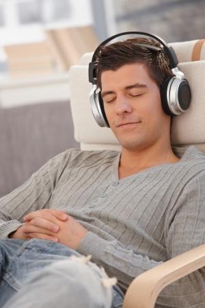 listening to music: Retrato de hombre joven sonriente con los ojos cerrados, escuchar m�sica a trav�s de auriculares en casa. Foto de archivo