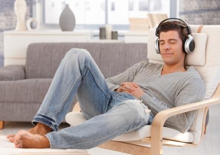 Guapo chico disfrutando de música en los auriculares, sentado en el sillón con ojos cerrados, sonriendo. Foto de archivo