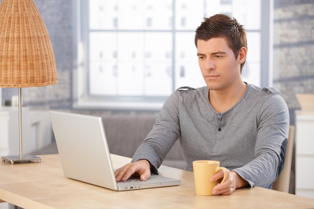 Young man concentrating on laptop computer screen, sitting at desk in living room, holding mug. photo