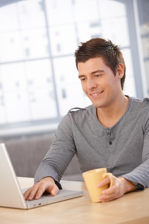 only young men: Smiling guy using laptop computer, looking at screen, having coffee at desk.