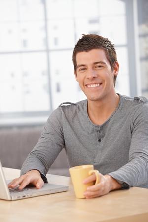 Happy young man sitting at table at home, smiling at camera, having tea, using laptop computer. Stock Photo - 8398187