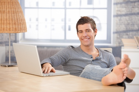 only young men: Portrait of young guy sitting at home with bare feet on table, using laptop computer, smiling at camera.