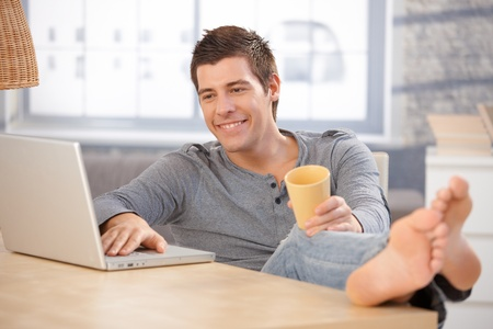 den: Laughing young man enjoying using laptop computer at home, holding tea cup, looking at screen with bare feet on table.