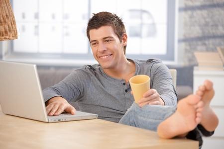 pies masculinos: Sonriente joven disfrutando mediante ordenador port�til en casa, sosteniendo la taza de t�, mirar la pantalla con los pies desnudos en la tabla.
