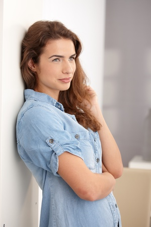 Young attractive woman standing at wall, smiling, looking away.