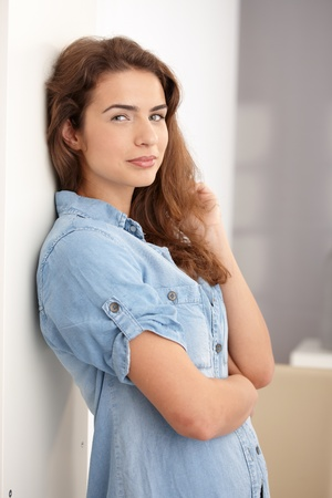 Attractive young woman standing arms crossed at wall, smiling. Stock Photo - 8549840
