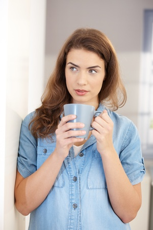 Attractive young woman drinking tea at home, standing at wall. photo