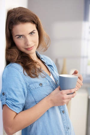 Attractive young female drinking tea at home, standing at wall. photo