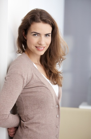 Happy young female standing at wall at home, smiling. photo
