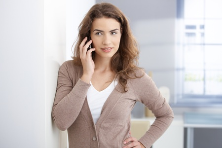 Pretty young girl chatting on mobile phone in liiving room, smiling. Stock Photo - 8558318