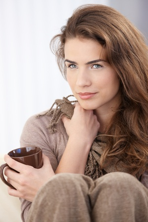 think through: Beautiful young woman sitting at home, drinking tea. Stock Photo