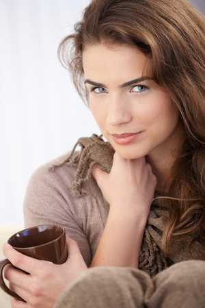 Attractive young female drinking tea, smiling. photo
