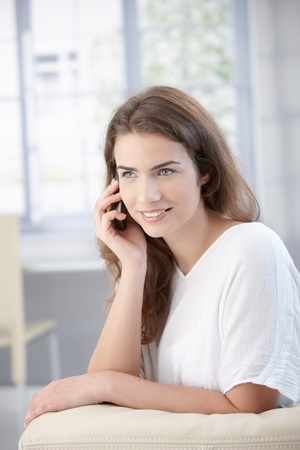 Attractive young woman talking on mobile, sitting on sofa at home, smiling. Stock Photo - 8552019