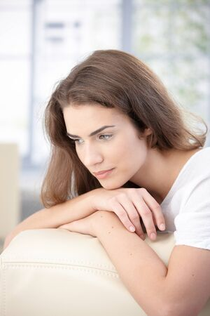 fantasize: Attractive young girl sitting on sofa at home, daydreaming.