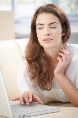 Attractive young woman browsing internet at home, laying on sofa. photo
