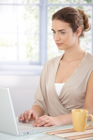 Attractive female using laptop at home, browsing internet. photo