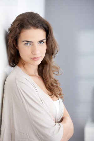 Portrait of beautiful young woman at home, leaning against wall. photo