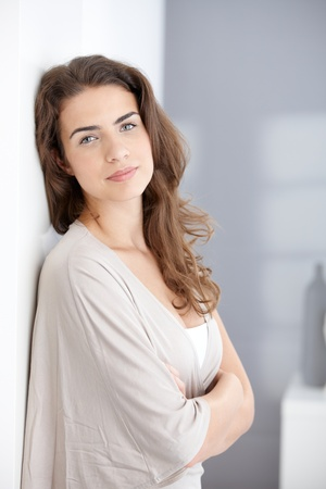 Attractive young female smiling at home arms crossed. photo