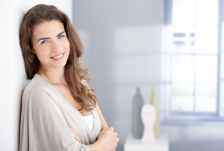 Attractive young woman smiling happily at home. photo
