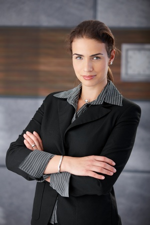 Young businesswoman smiling arms crossed in office lobby. photo