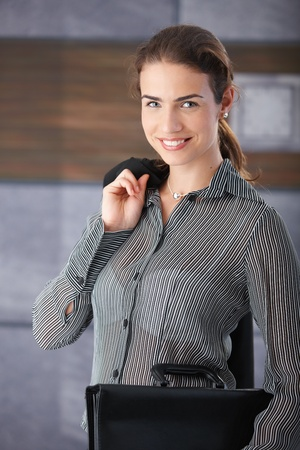 Attractive businesswoman smiling happily in hallway, holding briefcase, waiting for job interview. photo