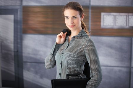 Attractive young businesswoman standing in office lobby, smiling, holding briefcase. photo