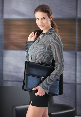 mini jupe: Pretty businesswoman smiling happily, holding briefcase, wearing mini skirt, going to job interview.