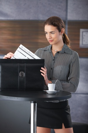 Attractive young businesswoman standing at table in hallway, packing briefcase. photo