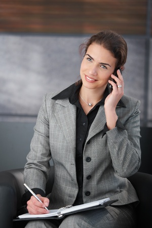 Young attractive personal assistant setting appointment on phone, smiling. Stock Photo - 8550132