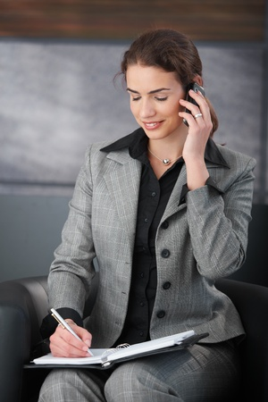 Young attractive secretary talking on phone, writing notes, smiling in trendy office. Stock Photo - 8550133