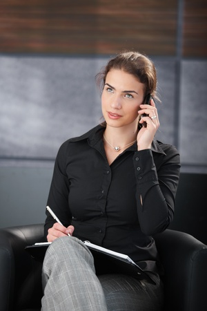 Attractive casual businesswoman talking on phone in modern office, writing notes. photo