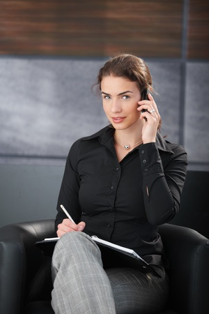 Attractive businesswoman chatting on mobile, writing notes, smiling in trendy office. photo