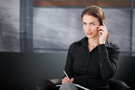 Attractive young secretary talking on cellphone, writing notes in elegant office. photo
