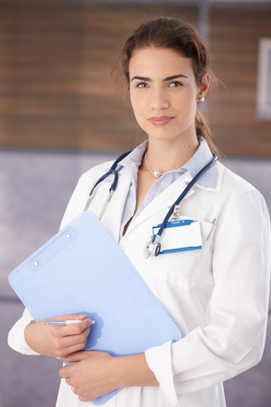 image consultant: Attractive young female doctor holding papers, standing in hospital corridor smiling. Stock Photo