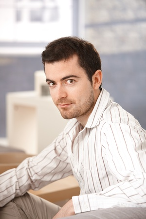 offish: Portrait of young man sitting at home.